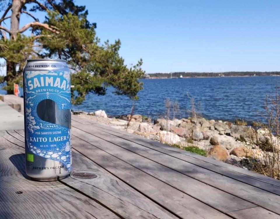 En ölburk på en terrass med vatten i bakgrunden.