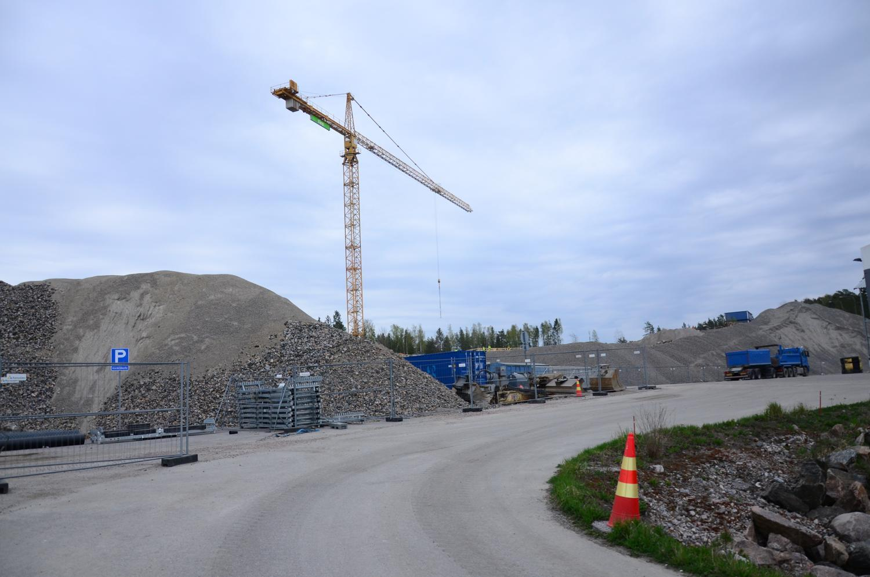 Bild av väg i förgrunden, grushögar och lyftkran i bakgrunden. Stor byggarbetsplats.