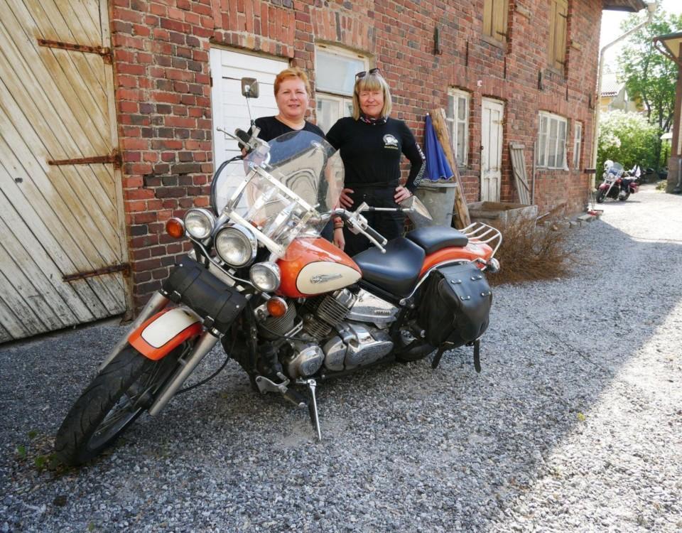 Två kvinnor står vid en motorcykel
