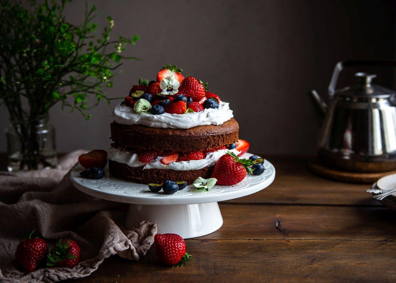 En chokladtårta med vispgrädde och bär.