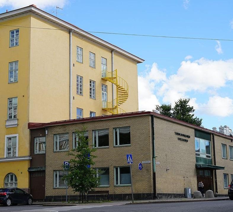 En gul skola med både äldre och nyare byggnad.
