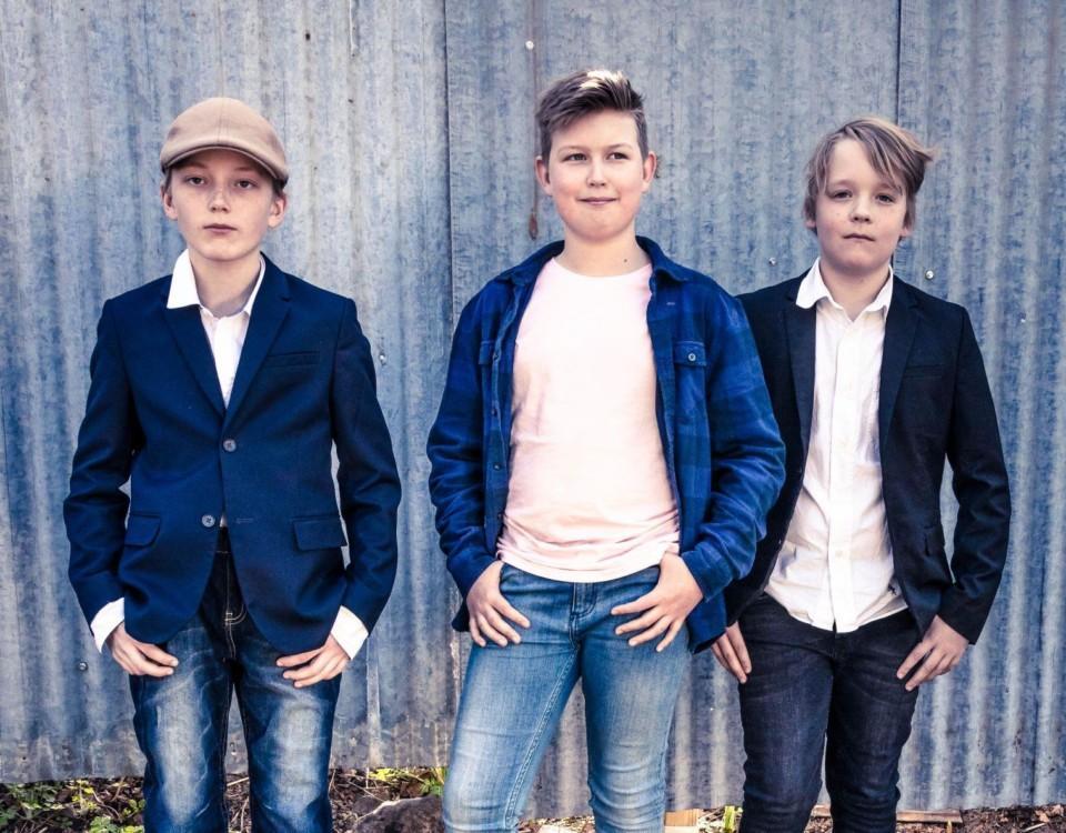 Tre pojkar står mot en vägg