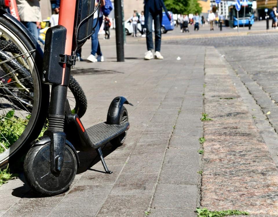 Elsparkcykel parkerad på trottoar.