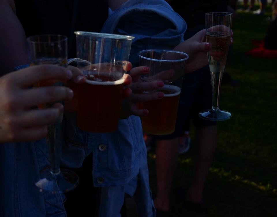 Ett par människor i skymning med ölstop och champagneglas i händerna.