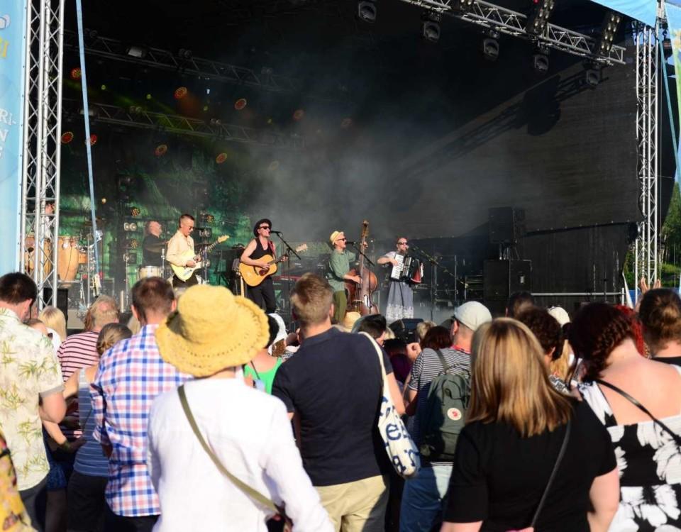 Ett rockband uppträder. Publik i förgrunden.