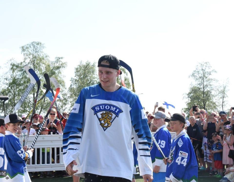 Ishockeyspelaren Kaapo Kakko iklädd Finlands vita spelskjorta stiger upp på scen på guldfesten i hans ära ordnad av Lundo kommun.