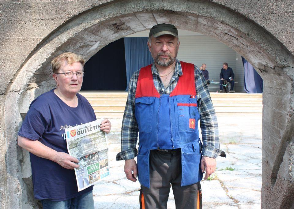 Runa Heino håller i Västanfjärds Bulletin och står bredvid Max Andersson, under en ruinport i sten.