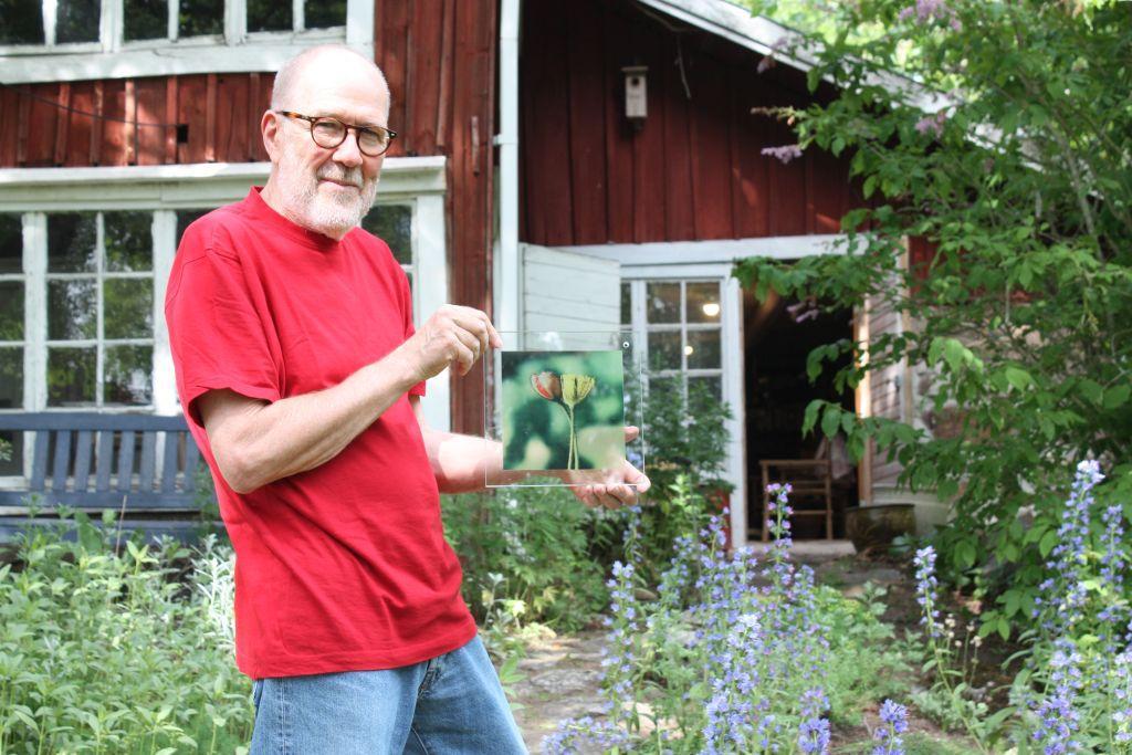 Janne Gröning håller i en glastavla med blomtryck, står utanför det röda huset i Westers Trädgård som han ställer ut i, grönt träd i bakgrunden och lila blommor runt omkring