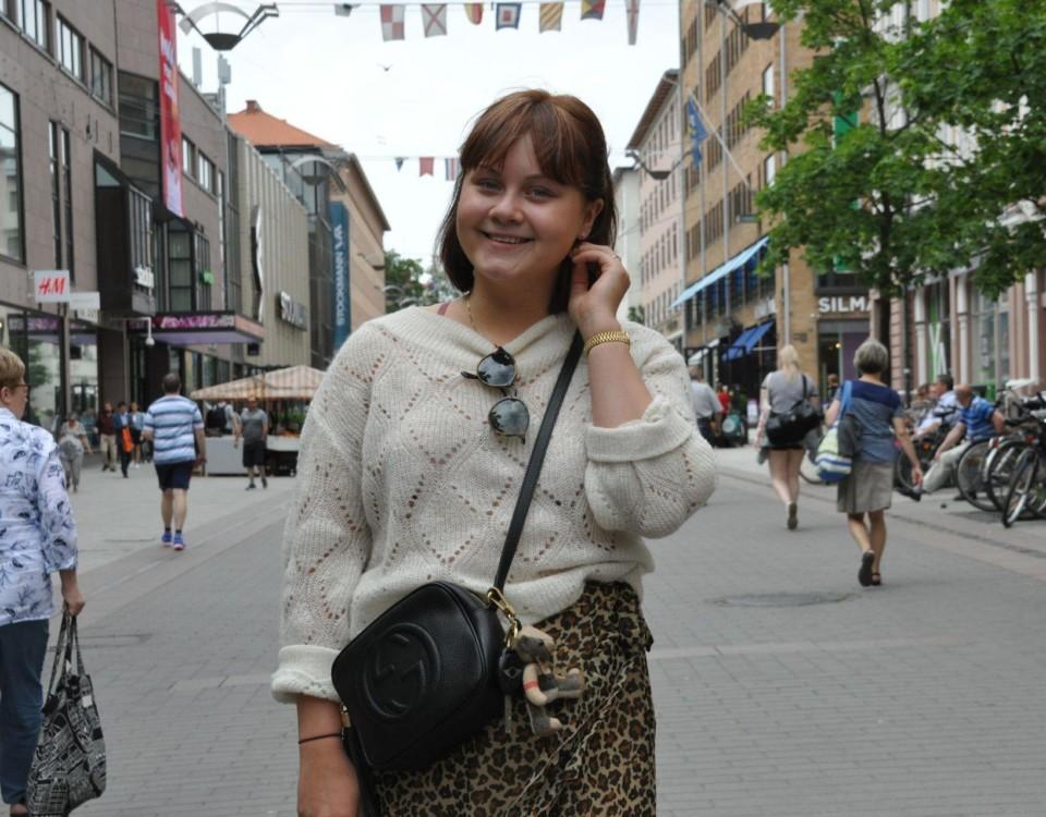 En leende kvinna står på gågatan i Åbo. I bakgrunden ser man ett myller av människor.