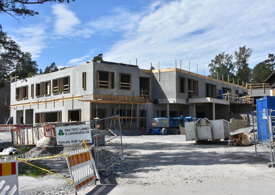 Början till ett tvåvåningshus som är under byggnadsarbete omringat av skyddsstaket och byggnadsmaterial.