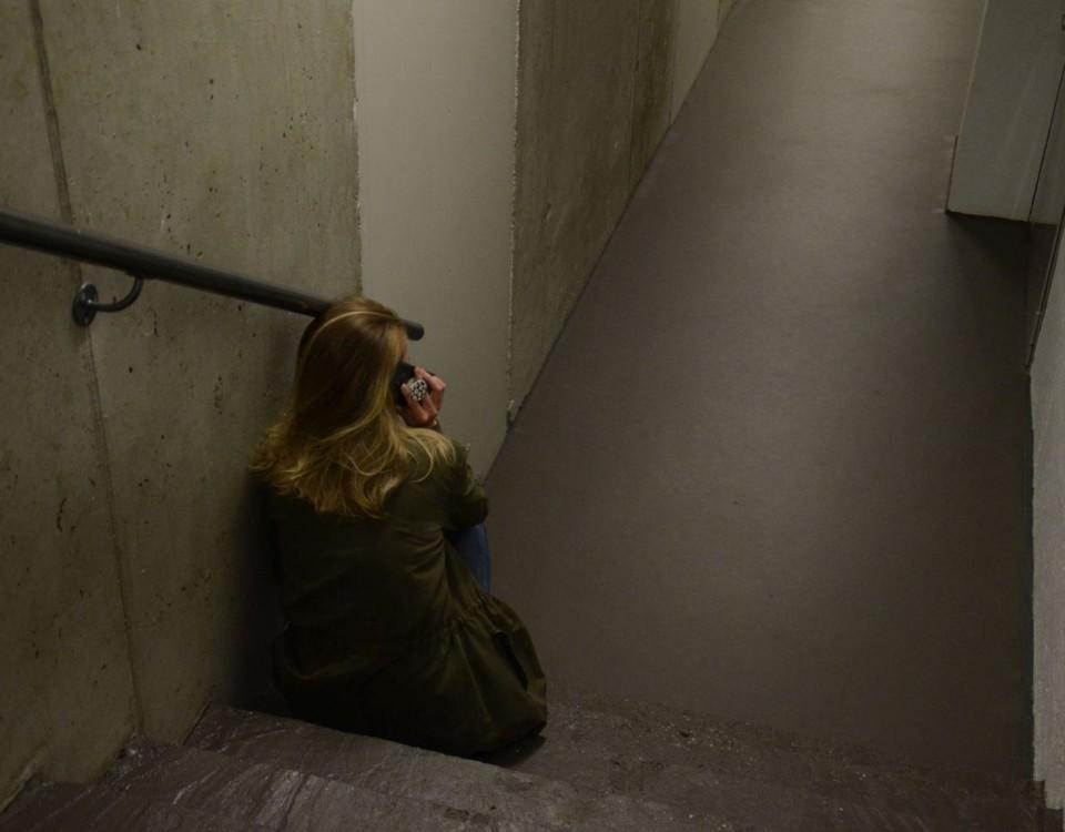 Kvinna sitter ensam och talar i telefon.