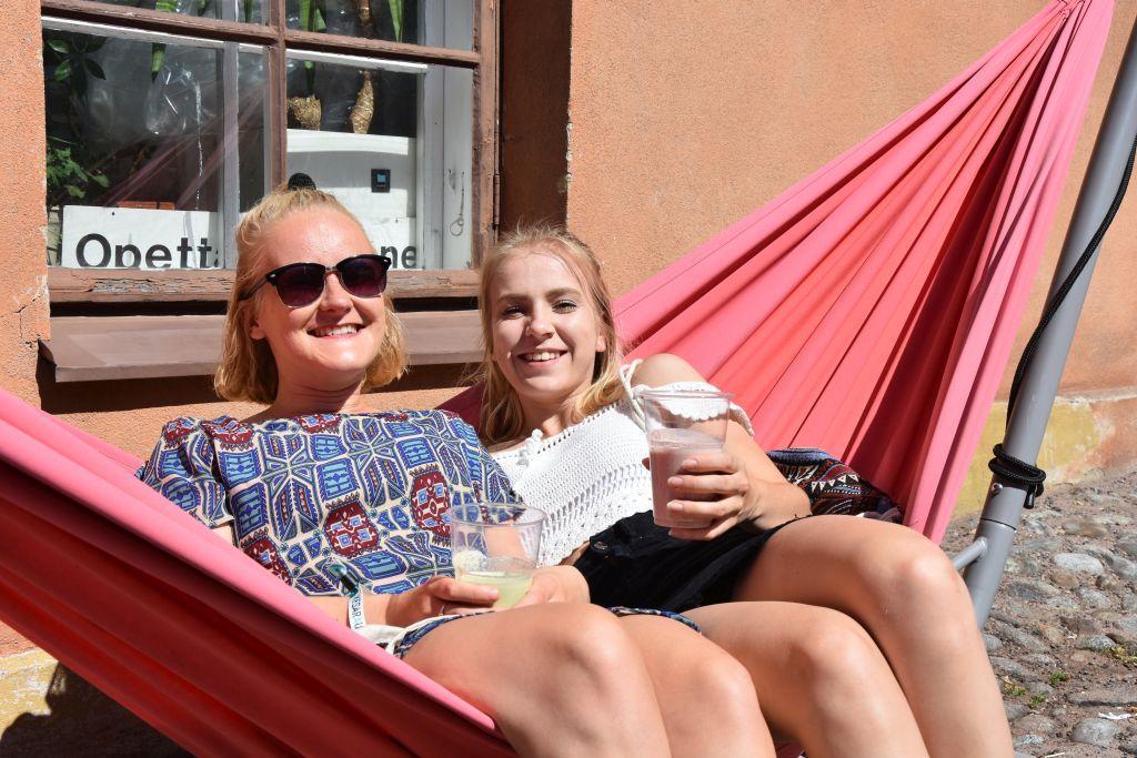 Två unga kvinnor sitter i en röd hängmatta och dricker smoothies.
