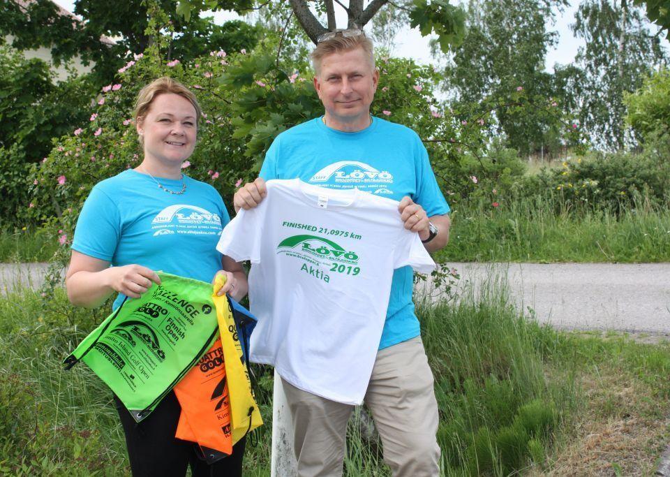 Netta Ratia-Dahlbom och Michael Nurmi är iklädda ljusblå broloppet t-skjortor och håller broloppet-påsar och t-skjorta i händerna. I bakgrunden gröna buskage