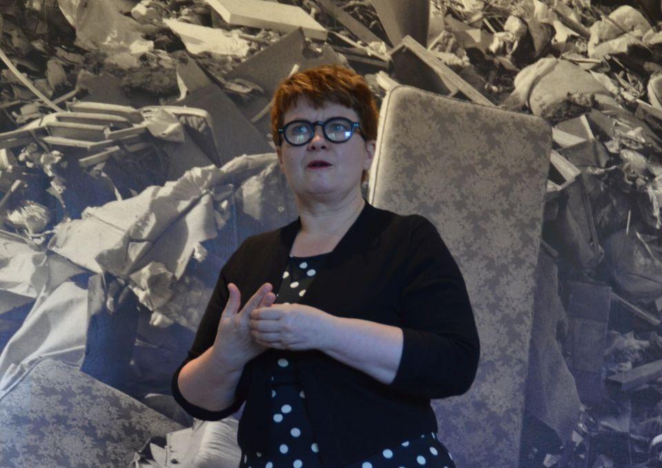 En kvinna står och pratar och gestikulerar framför ett fotografi av en avstjälpningsplats.