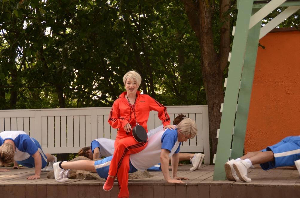 Dansande gymnastikklädd kvinna framför barn som gör armhävningar.