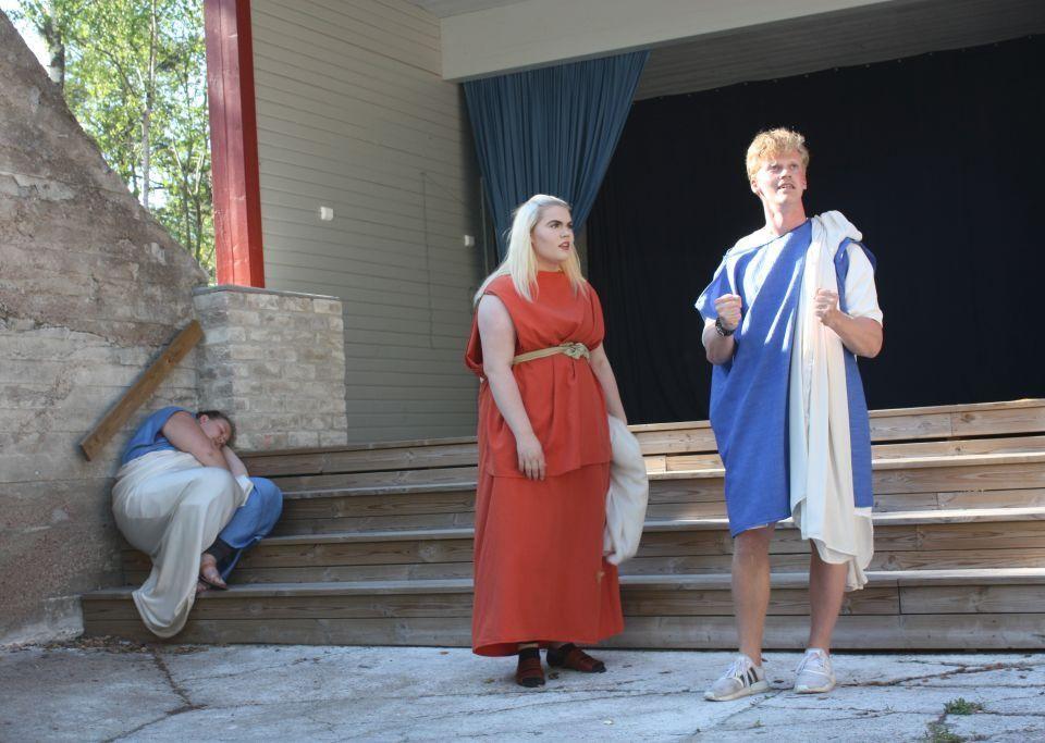 Alice Ekholm klädd i röd klänning och Jesper Lindblom klädd i blå dräkt står framför Kalkholmsestradens trappa. Fanny Stenström sitter på trappan bakom dem.