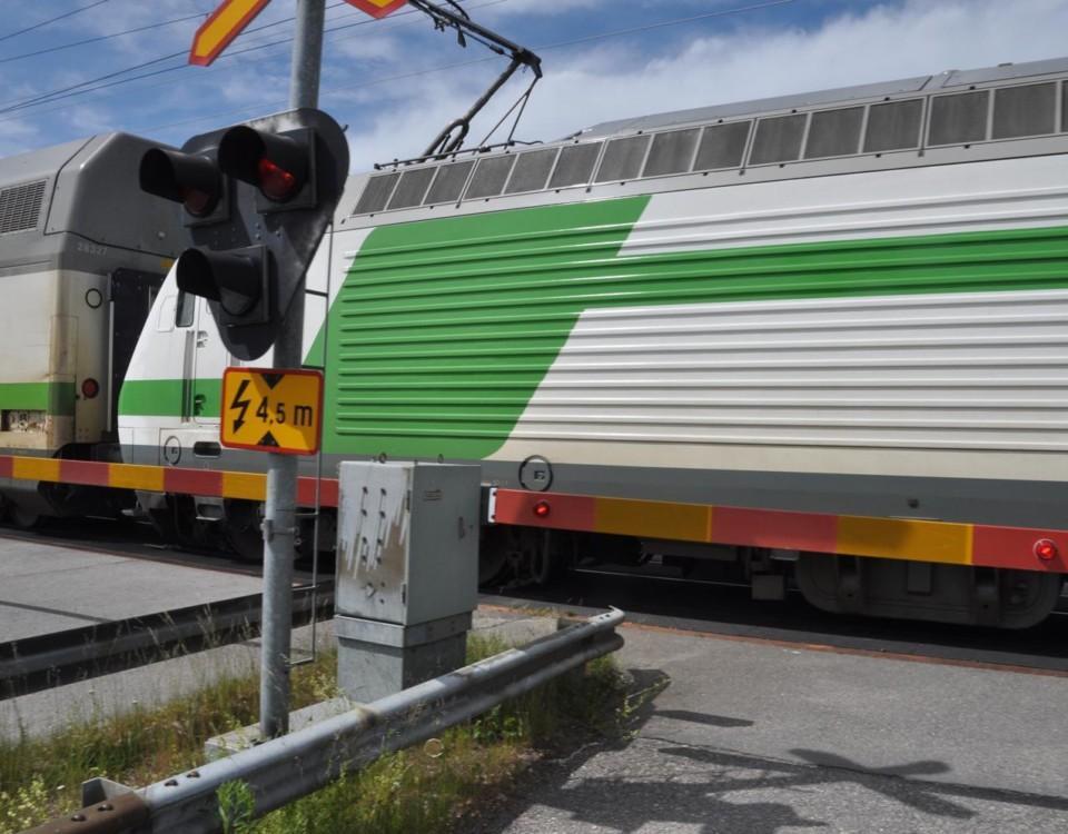 Tåg passerar övergång med bommar