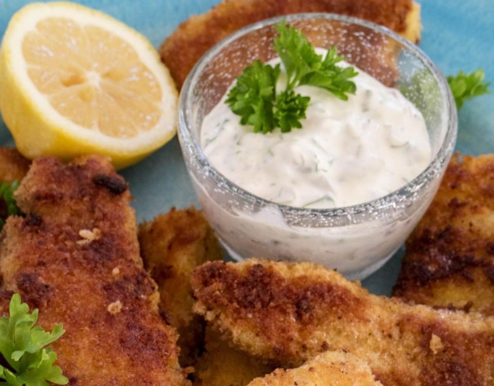 Fiskpinnar, en skål med sås och en citron.