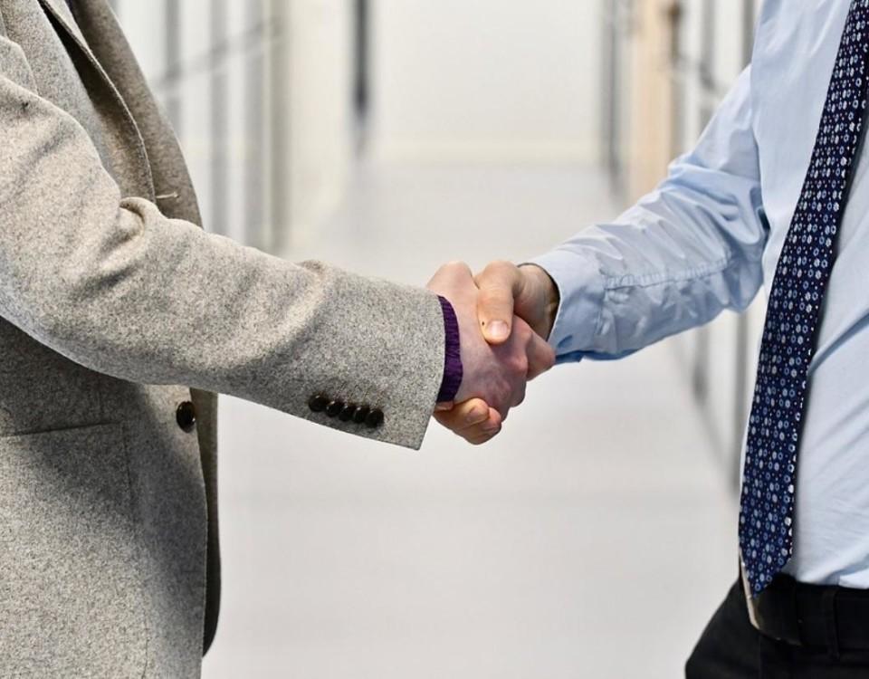 Två kostymklädda män skakar hand