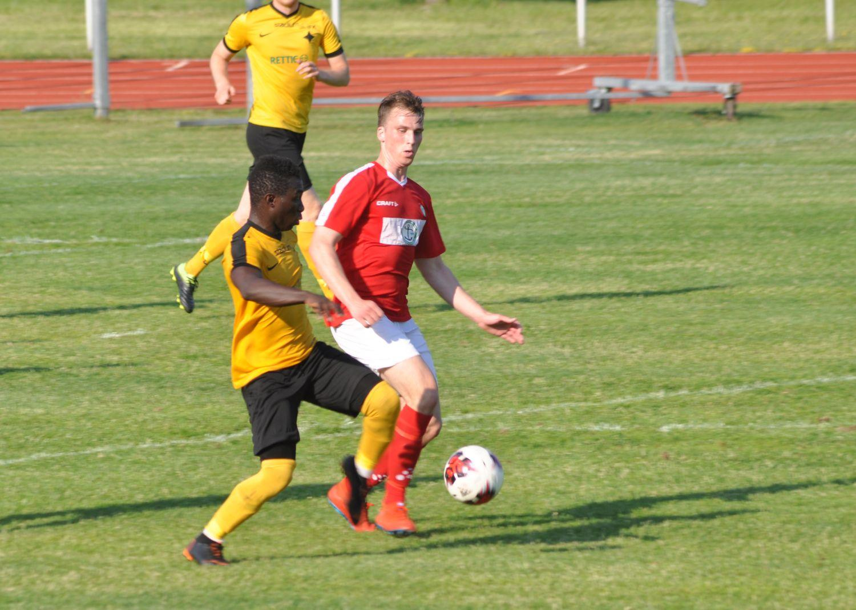 Två fotbollsspelare kämpar om bollen