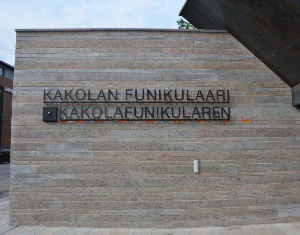 Texten Kakolanfunikulaari och Kakolafunikularen monterade på väggen vid ingången till snedhissen