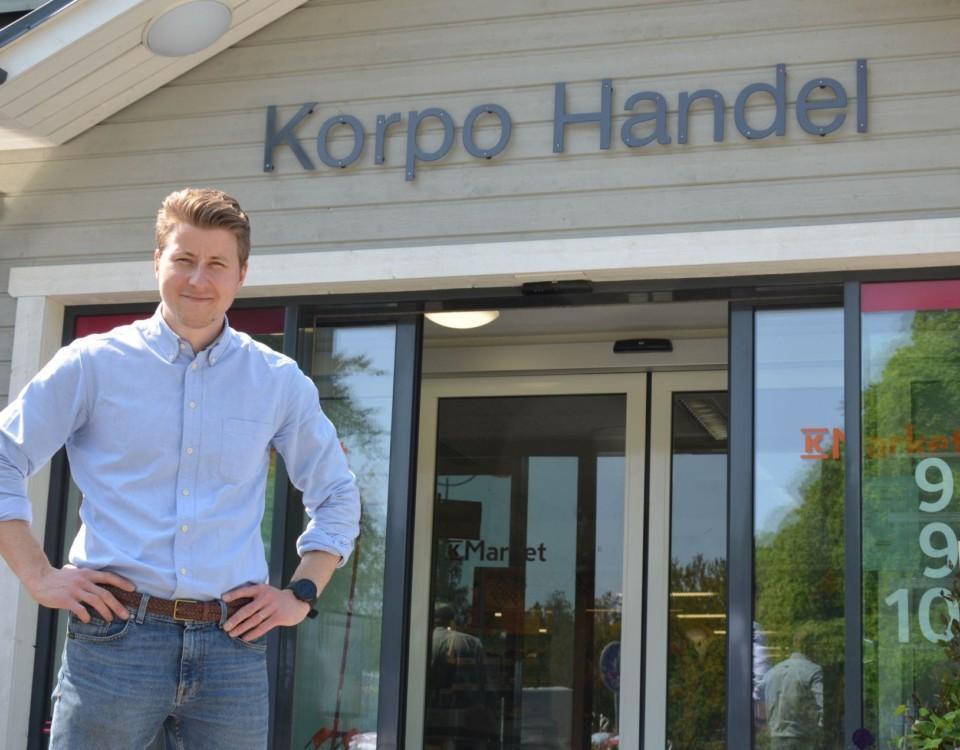En man står framför ingången till matbutiken Korpo Handel.