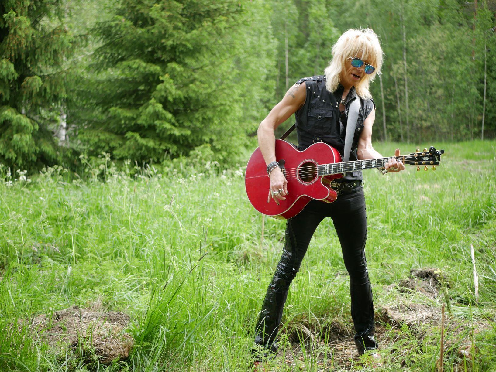 Rockartist med gitarr i skogen