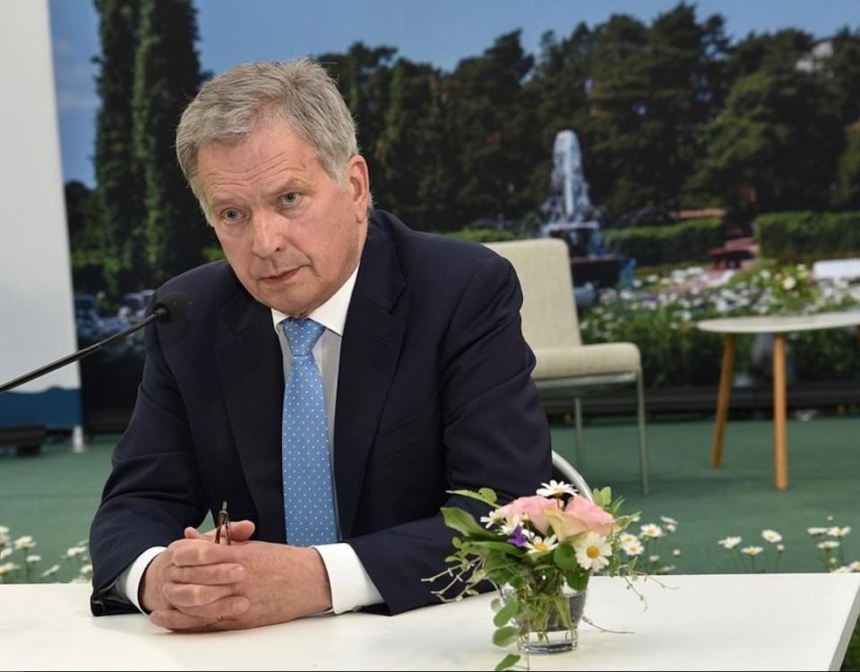 Finlands president sitter vid ett bord