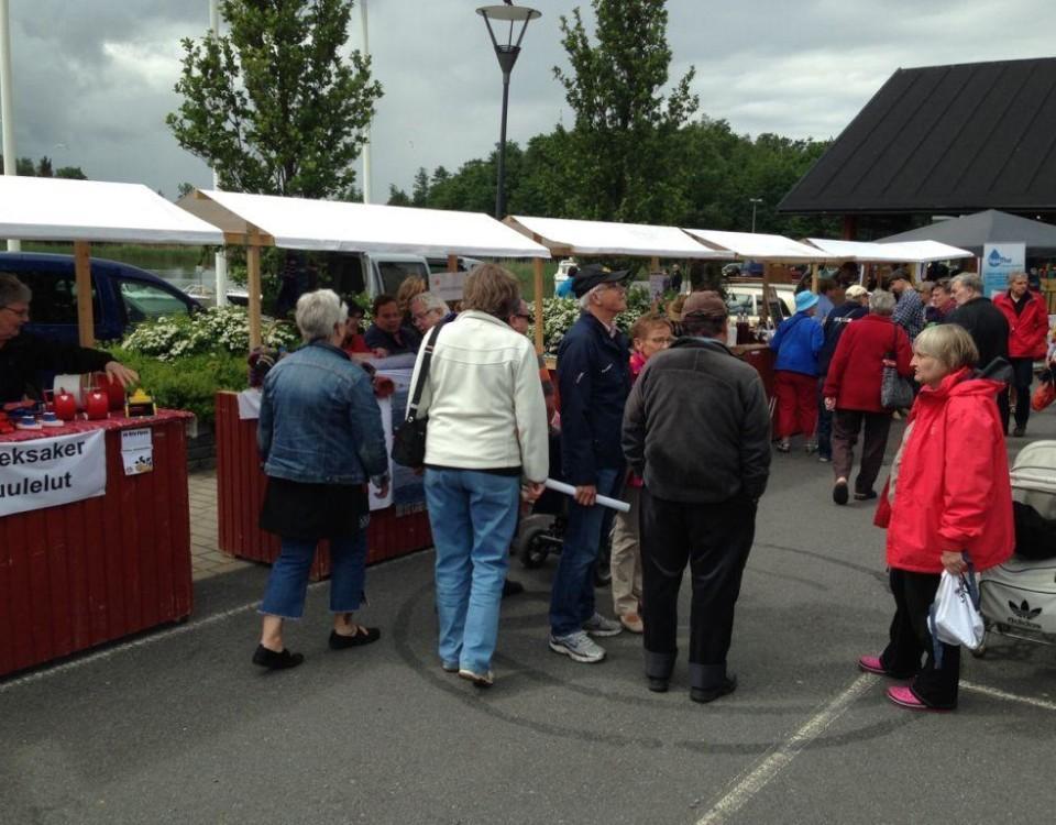 Människor som besöker en marknad. Röda stånd med vita soltak.