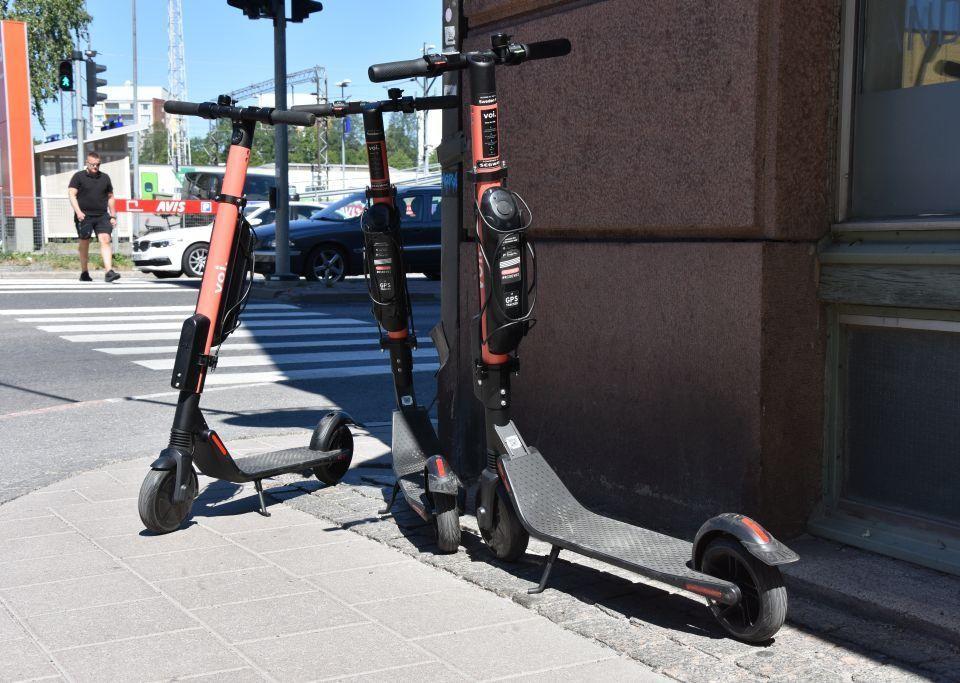 Tre elsparkcyklar står parkerade på trottoaren i ett gathörn