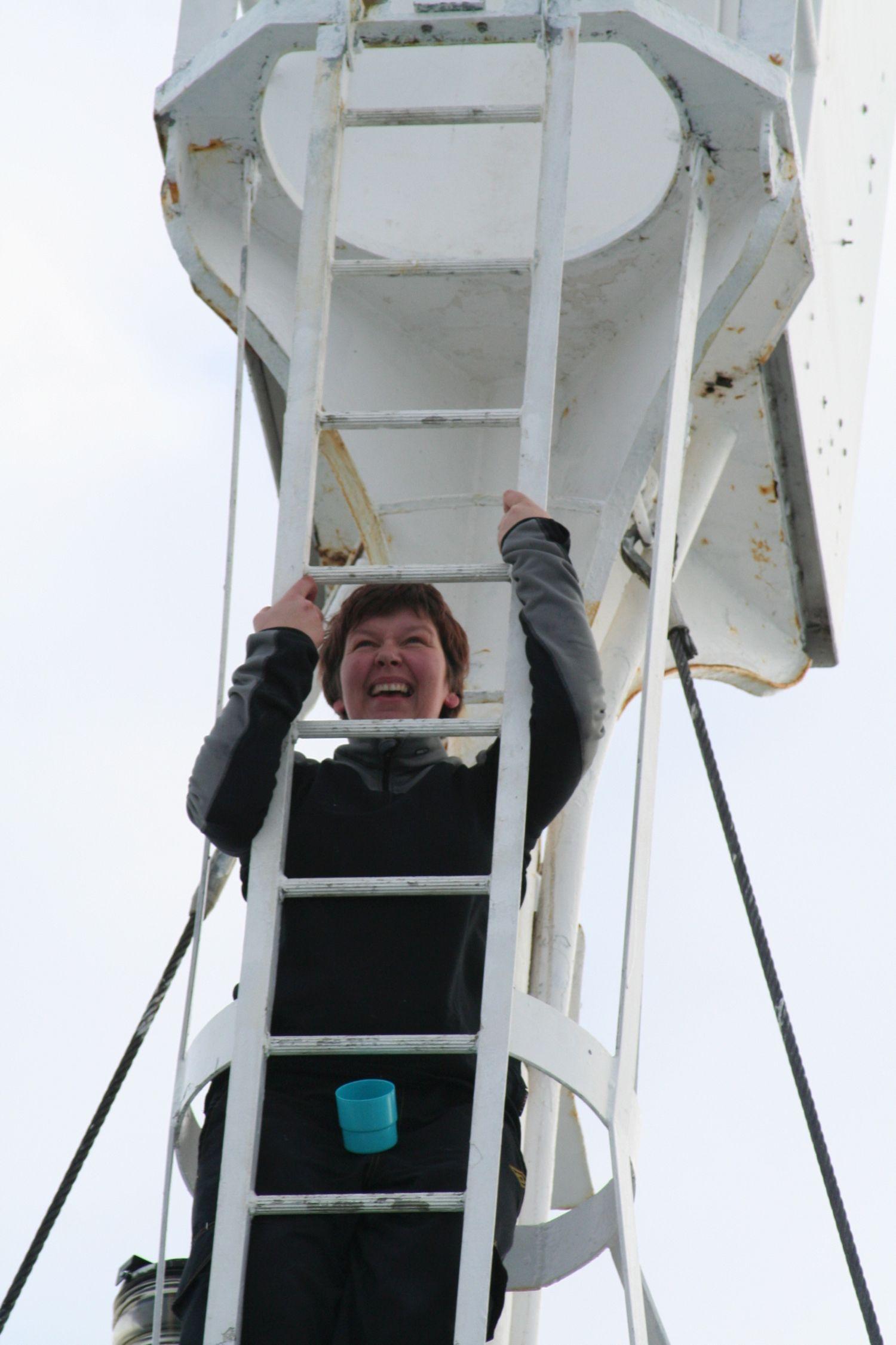 Anita Storm skrattar mot kameran medan hon klättrar upp för en stege ombord på en båt i ishavet.