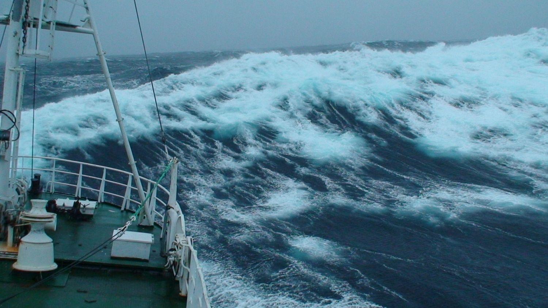 Stora gråa vågor och fören på en båt syns på bilden.
