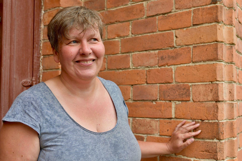 Anita Storm står framför en tegelvägg.
