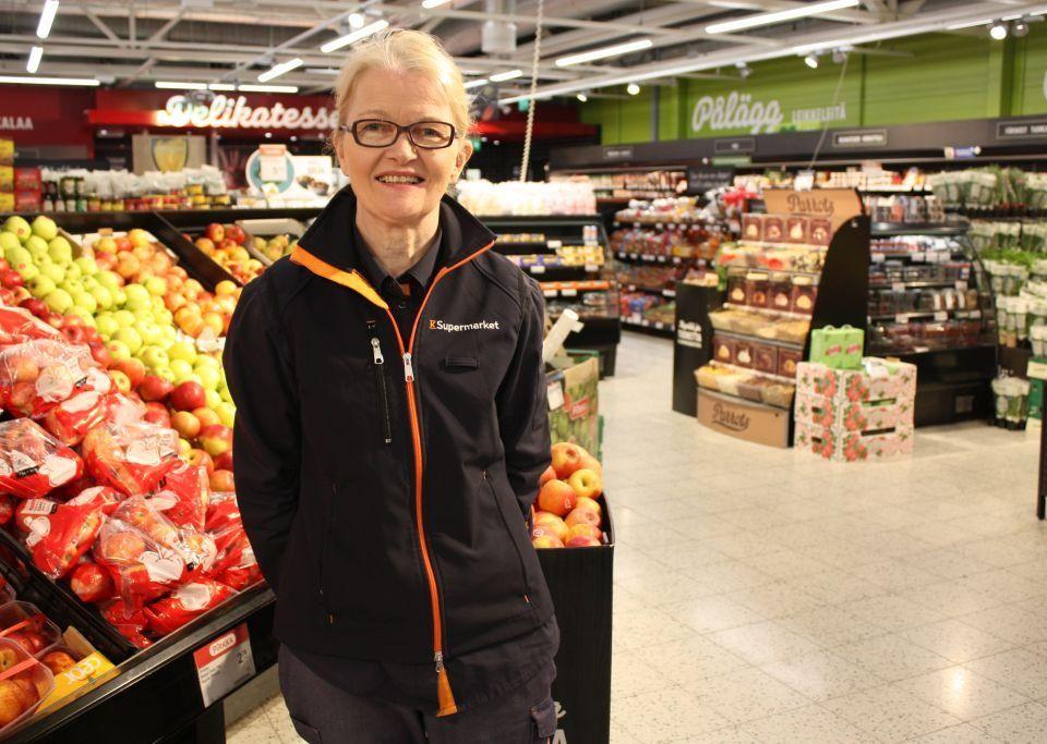 Anne Nyman står vid frukt- och grönskaksavdelningen i K-Supermarket, bredvid äpplena.