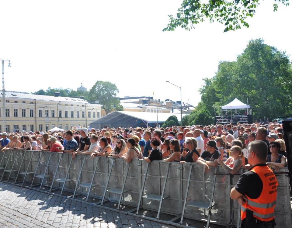 En stor folkmassa på en festival bakom ett staket.