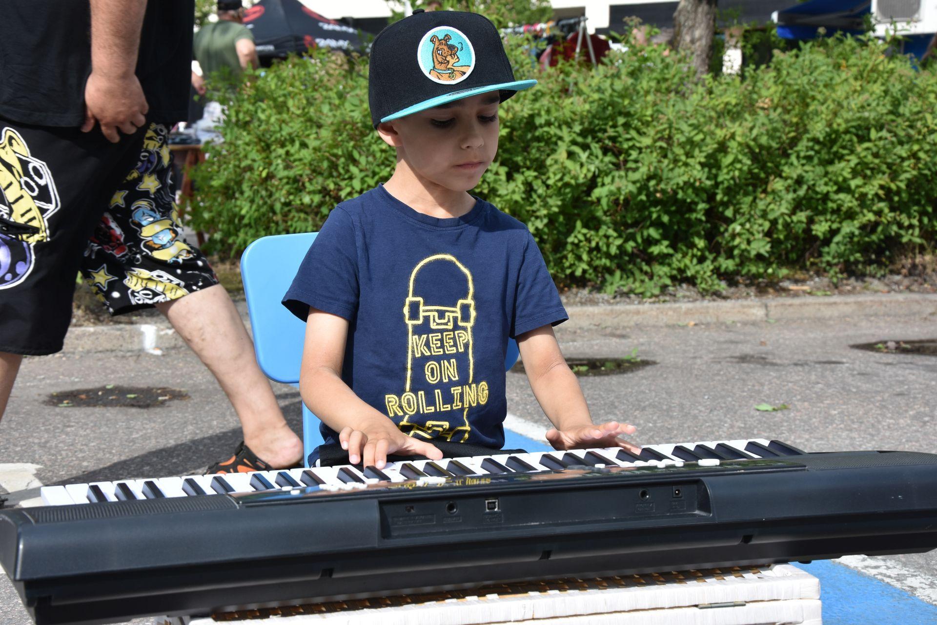 En liten pojke sitter ute på ett torg och spelar på en synt.