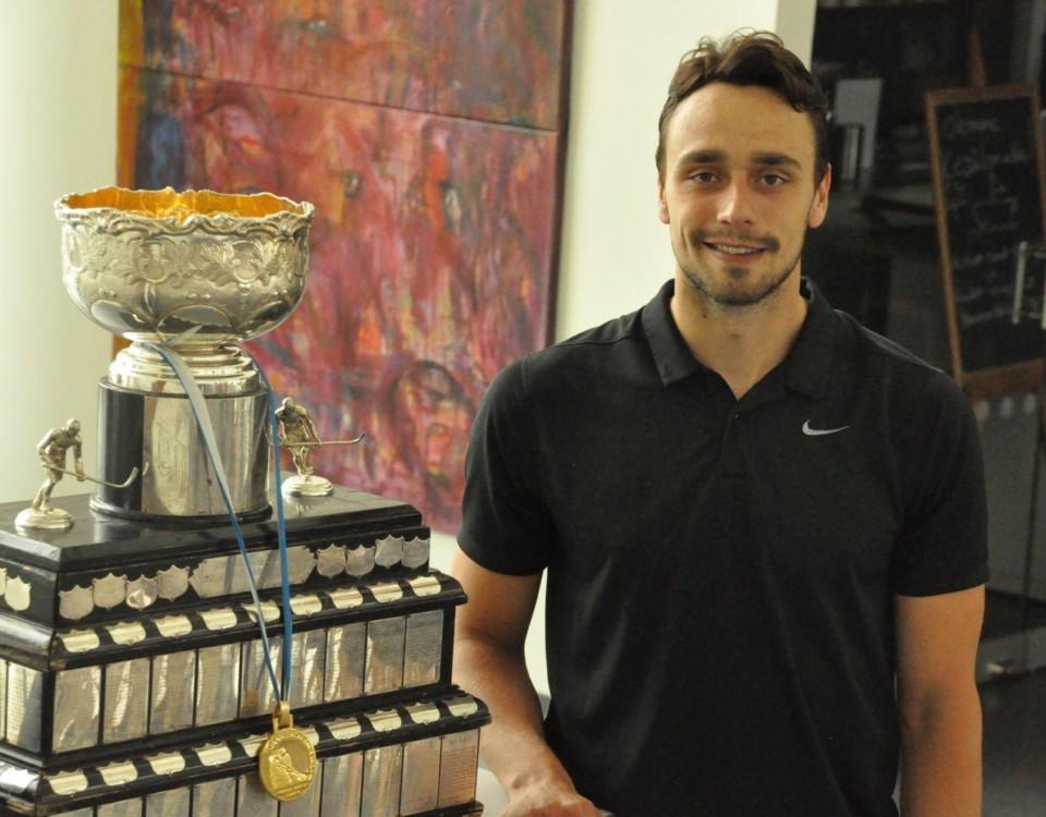 Ishockeyspelaren Niklas Friman poserar med en pokal på biblioteket i S:t Karins