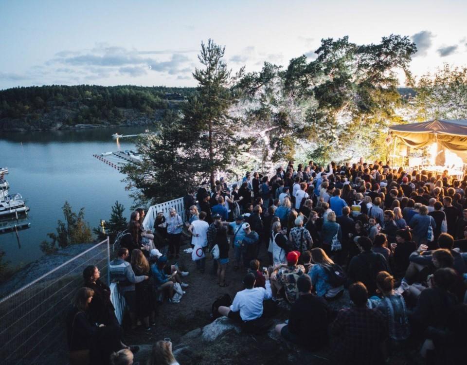 Folkmassa på festivalområdet intill havet, i skymningen.