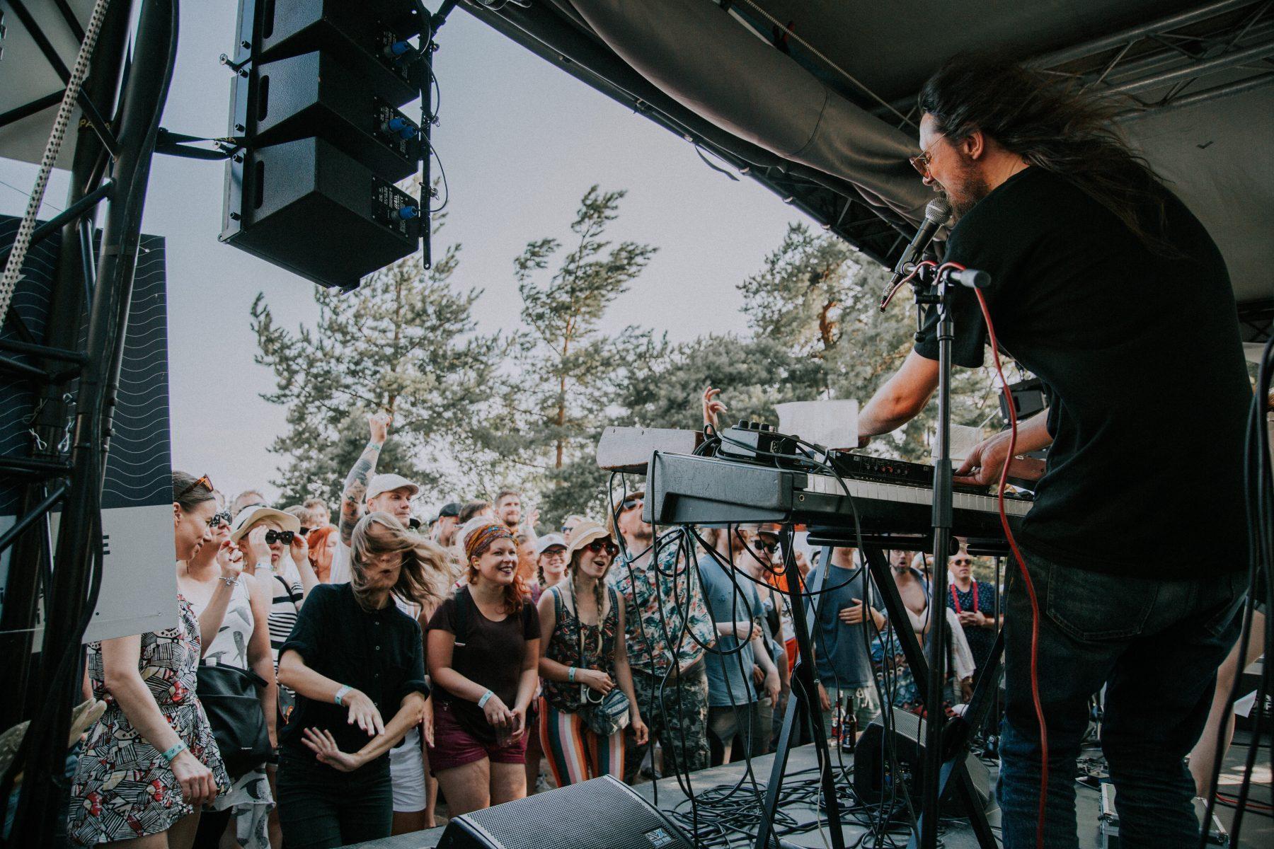 En manligt artist står på scenen och spelar synt. Det långa svarta håret fladdrar och publiken dansar för fullt.