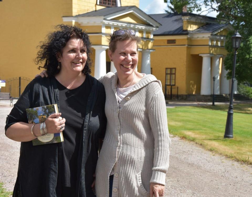 Två kvinnor står och håller om varandra utanför stora gula stenhus.