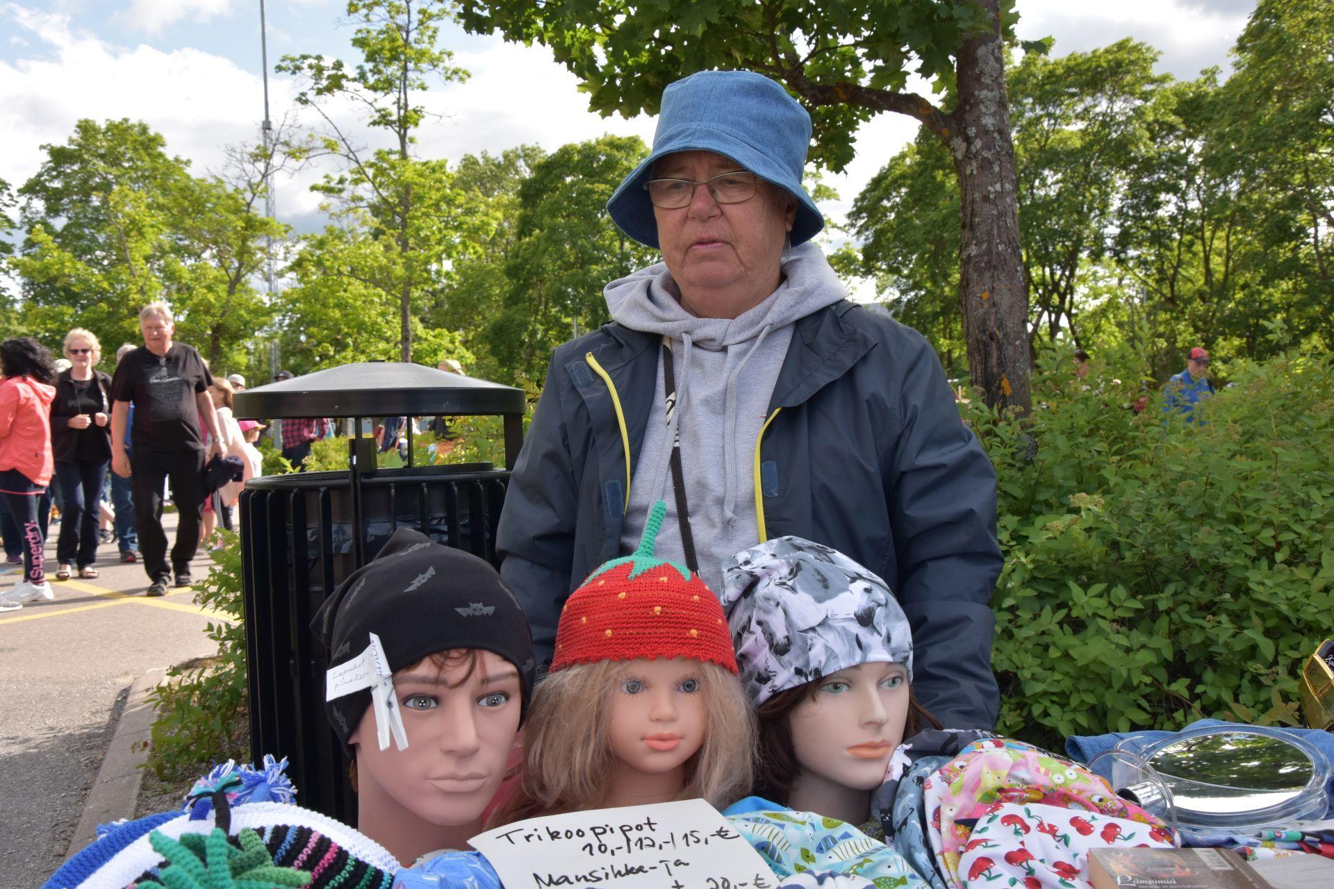 En äldre dam står vid ett bord där ett utbud av hattar finns framställt. Tre mannekäng huvuden med olika hattar på står på bordet.