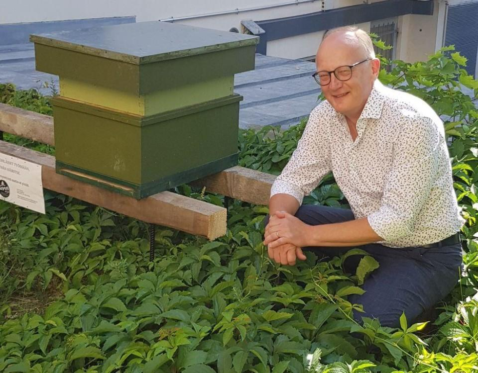 En man sitter hukad intill en bikupa