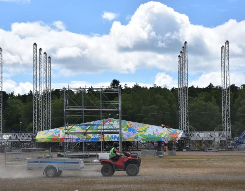 En festivalscen håller på att byggas. Scenen har fortfarande inget tak och framför scenen kör en person klädd i arbetskläder på en fyrhjuling.