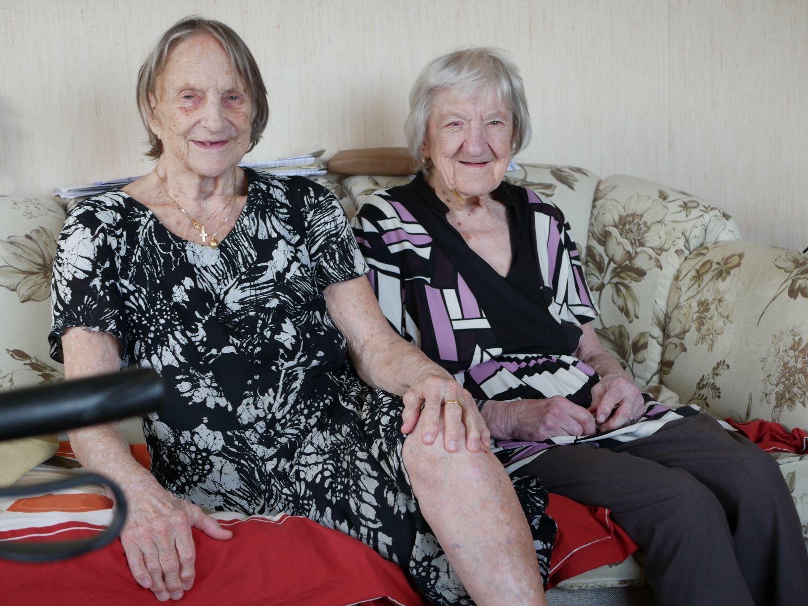 två äldre kvinnor sitter i en soffa