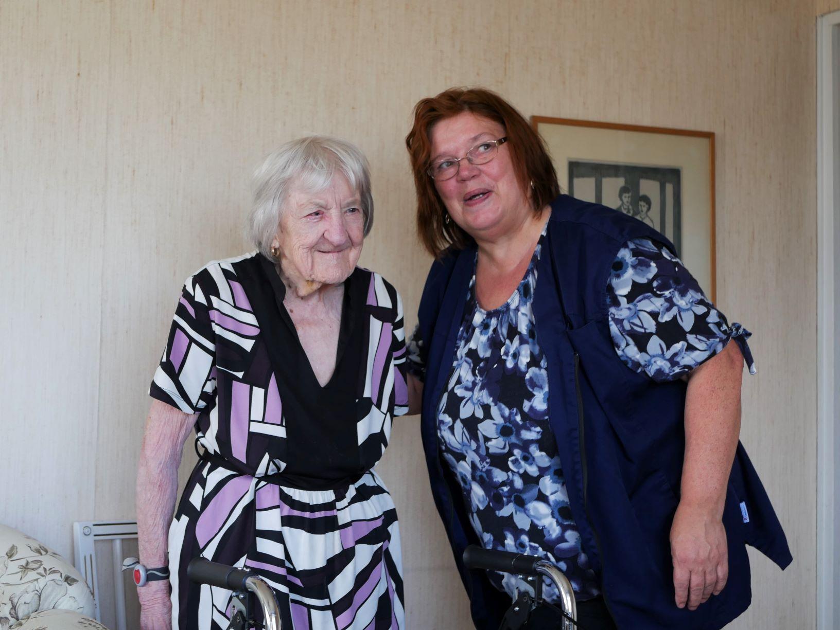 En äldre person står bredvid vårdaren