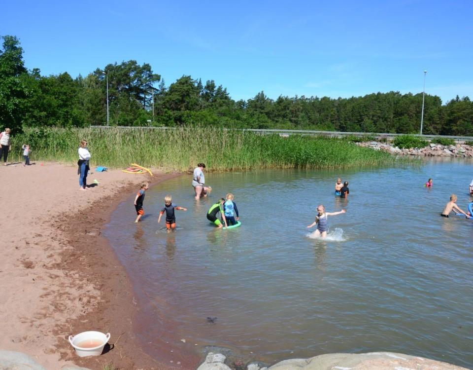Ett tiotal barn plaskar runt i vattnet vid Kannvik badstrand.
