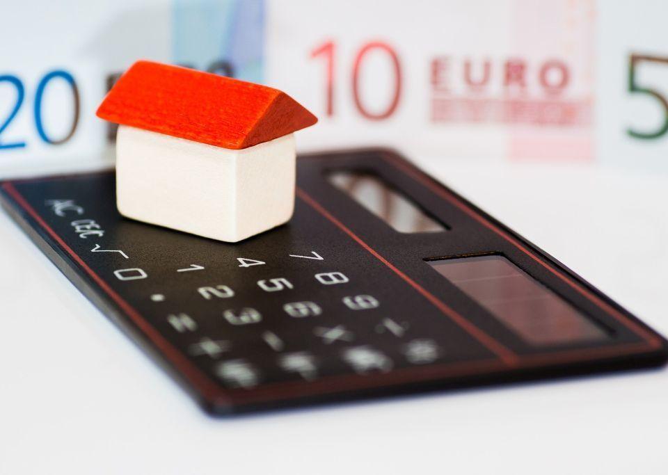 Bild av pengar, en kalkylator och ett animerat hus.