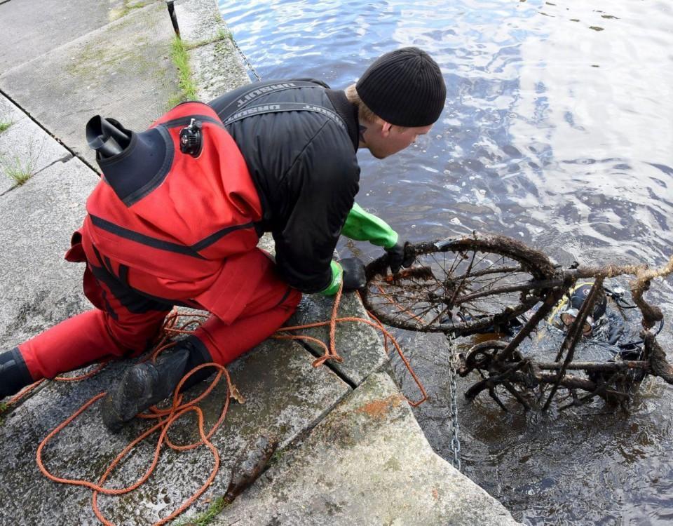 Man lyfter cykel ur vatten