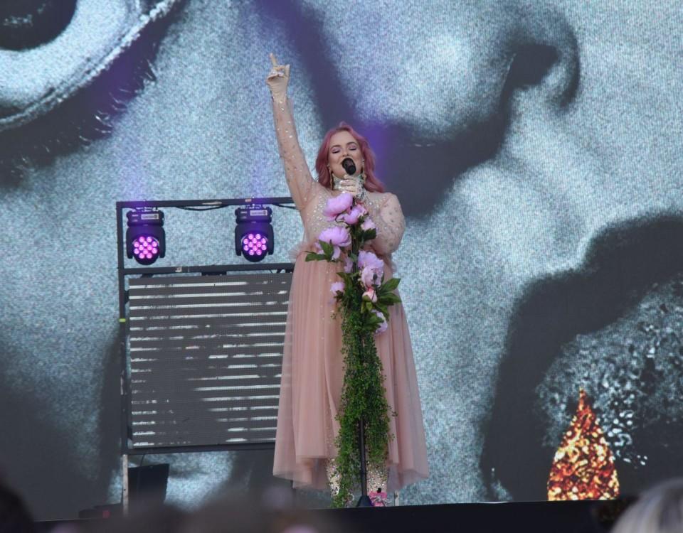 En kvinna i en ljusröd klänning står på svenen med en hand uppsträkt i luften
