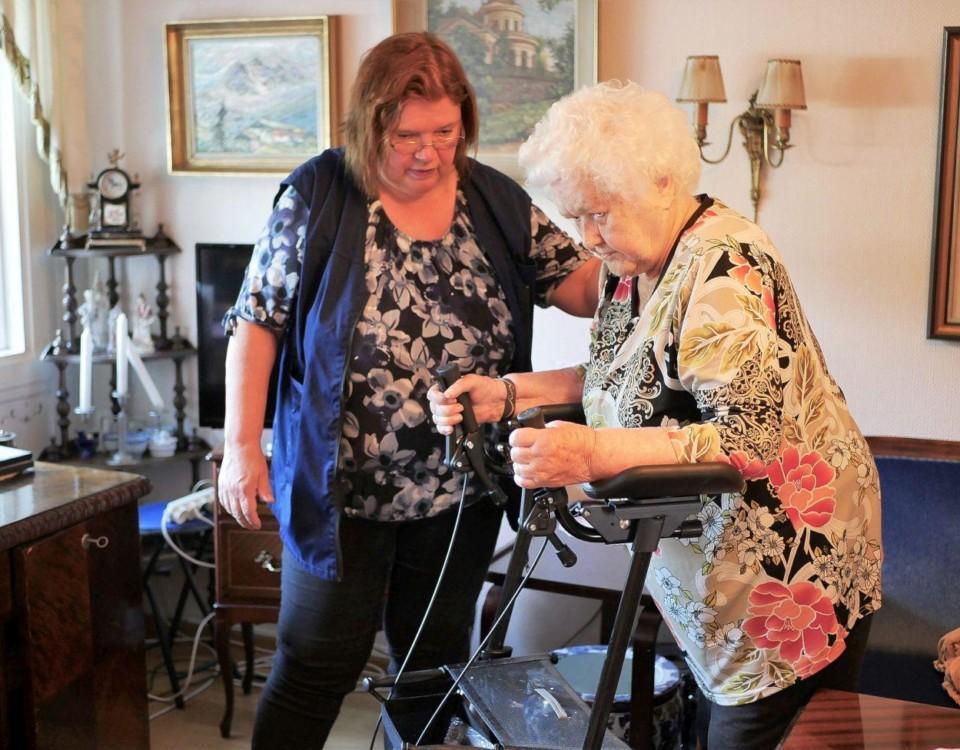En närvårdare hjälper en äldre dam som rör sig med rullator.